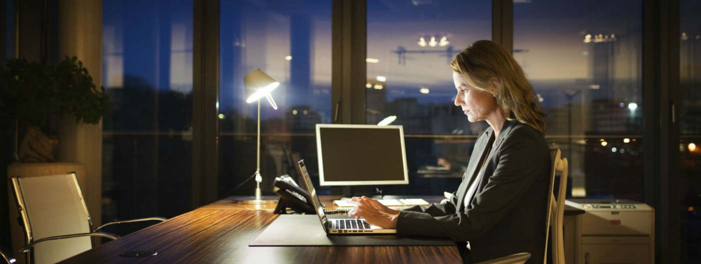 Mature-Business-Woman-Working-Late-1600×841